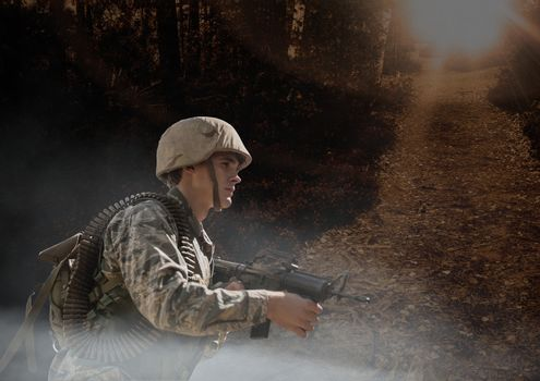 Soldier man holding a weapon against woods