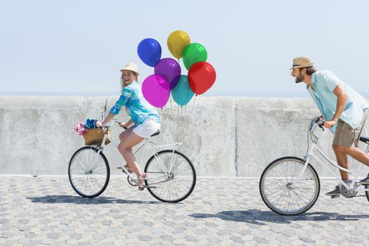 Couple cycling with balloons in sunshine