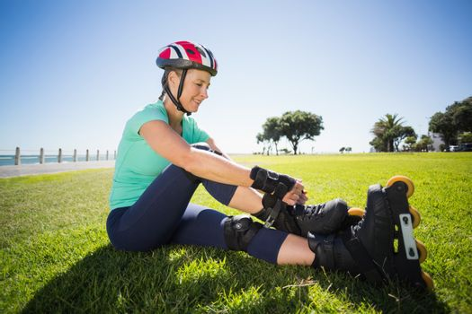 Fit mature woman tying her roller blades on the grass