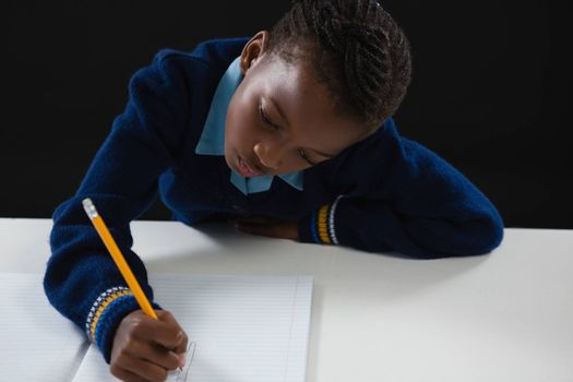Attentive schoolgirl doing his homework against black background