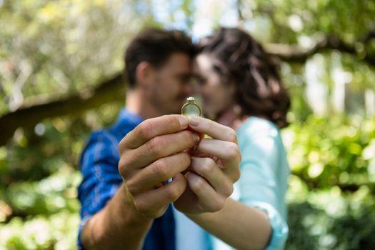 Couple holding engagement ring
