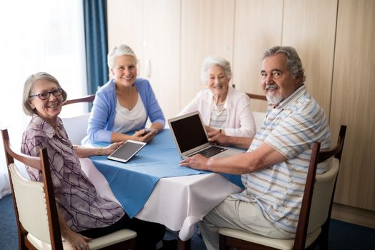 Smiling seniors sitting with technologies at table in retirement home