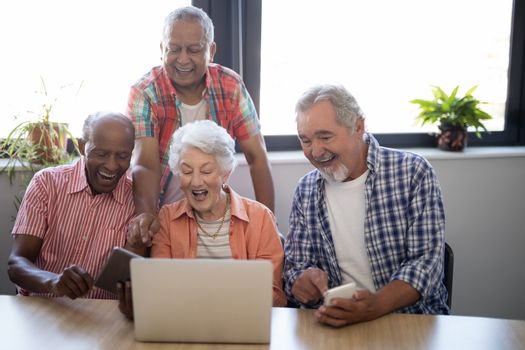 Happy senior people using technology while sitting at table against window in nursing home