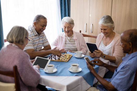 Senior friends playing chess and using technology while having coffee at table in nursing home