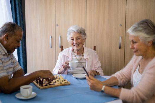 Smiling woman having coffee while sitting with friends playing chess and using technology at table in nursing home