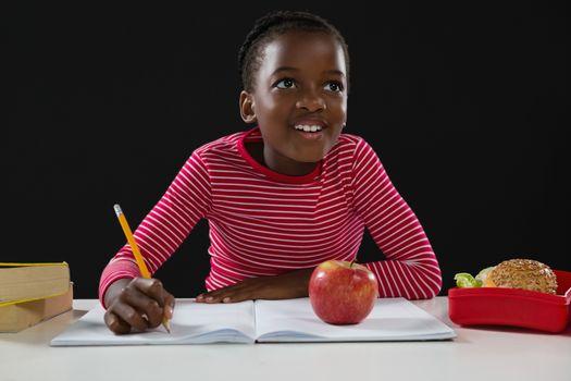 Smiling schoolgirl doing her homework against black background