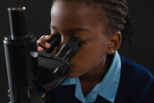 Attentive schoolgirl using microscope against black background