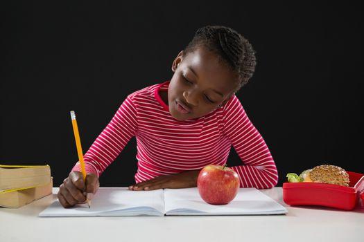 Attentive schoolgirl doing her homework against black background