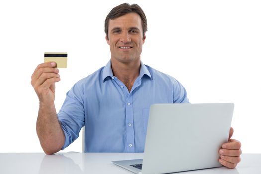 Male executive holding debit card against white background