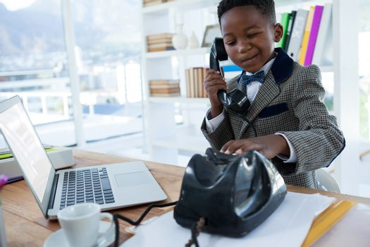 Thoughtful businessman making face while dialing telephone