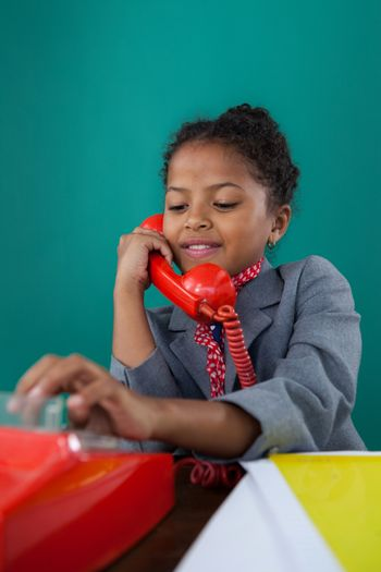 Close up of smiling businesswoman dialing numbers on land line phone