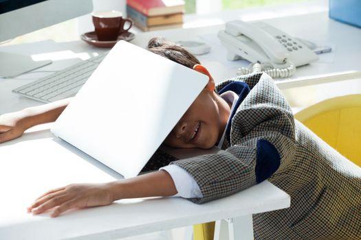 Businessman taking nap on laptop at desk
