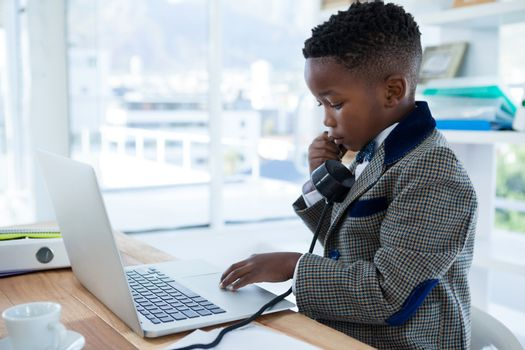 Businessman scrolling on laptop while using telephone