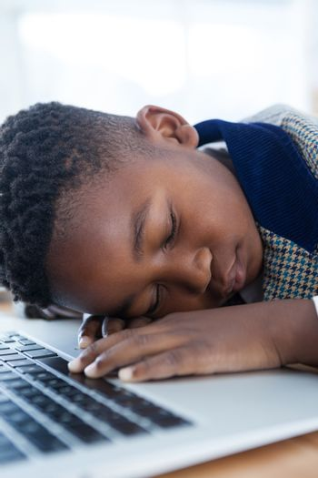 Close-up of businessman taking a nap on laptop at desk
