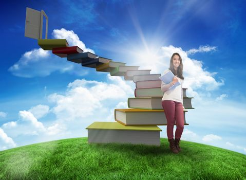 Composite image of smiling student holding textbook