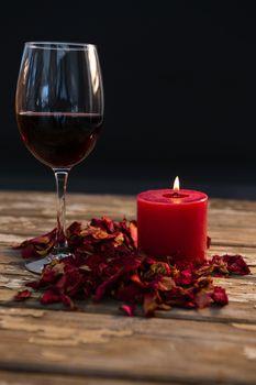 Wineglass by illuminated candle