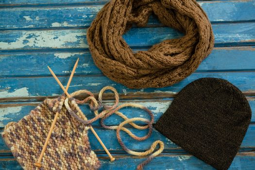 High angle view of muffler with knit hat and knitting needles