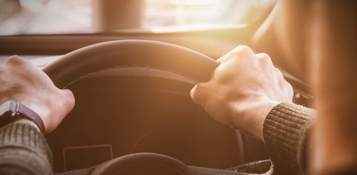 man holding the steering wheel of his car