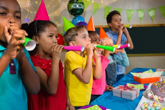 Playful kids blowing party horns