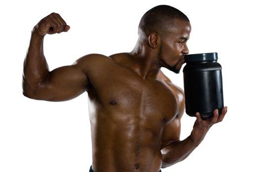 Shirtless sports man kissing supplement jar