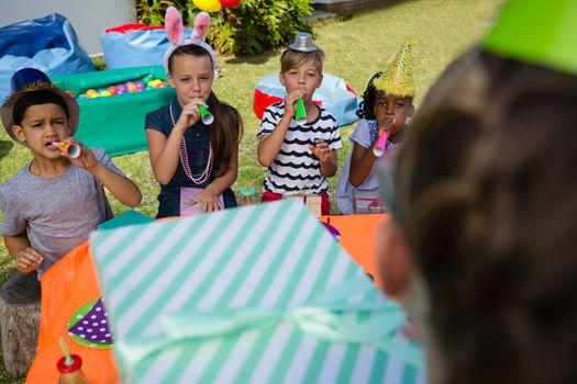 Children blowing party horn