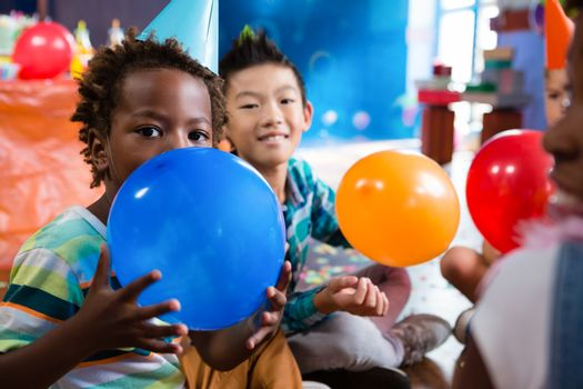 Portrait of children playing with colorful balloon