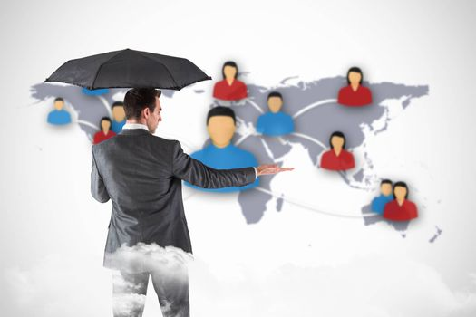 Businessman holding an umbrella with hand out against view of communication network
