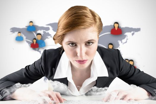Redhead businesswoman sitting at desk typing against view of communication network