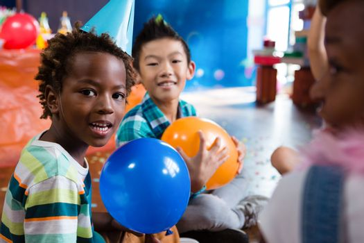 Portrait of children playing with balloon