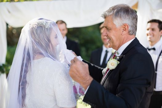 Happy father removing veil of his daughter