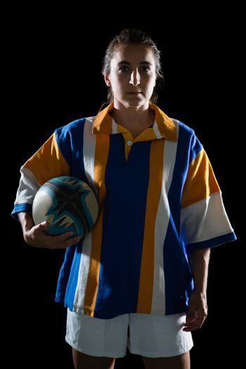 Portrait of female athlete in sports clothing holding rugby ball