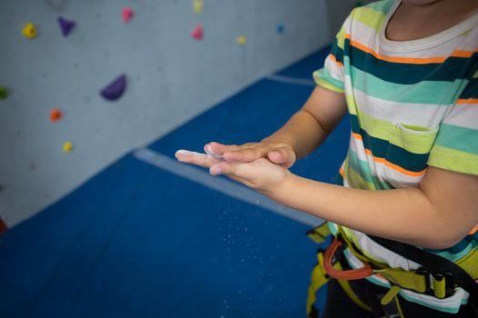 Boy rubbing powder on hands in studio