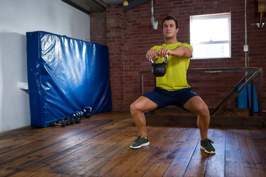 Determined man exercising with kettlebell