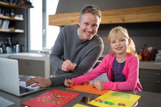 Father and daughter posing while coloring