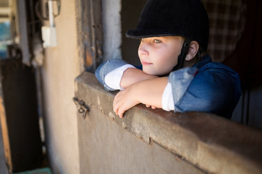 Girl leaning on wall in the stable