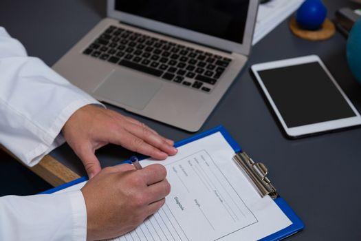 Physiotherapist writing prescription on clipboard