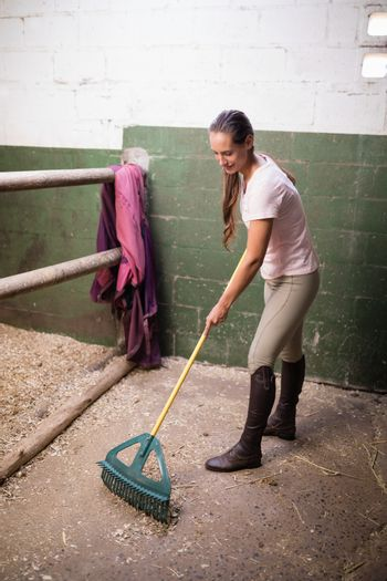 Female jockey cleaning stable