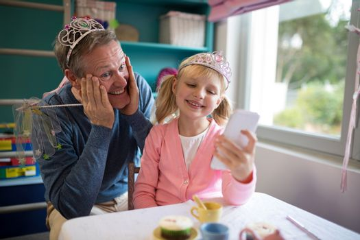 Father and daughter in fairytale dressing taking a selfie