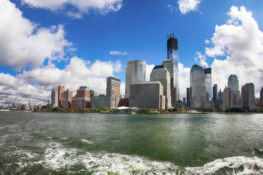 A shot from a ferry looking back at Manhattan skyline. The water shows trace left by the ferry boat.