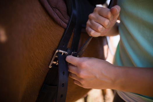 Mid section of female jockey fastening saddle