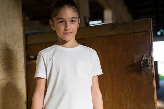 Girl standing in stable