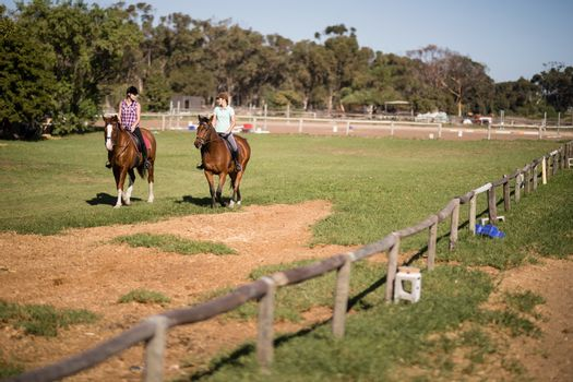 Mid distant view of female friends horseback riding