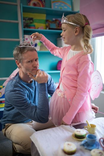 Father and daughter in fairytale dressing playing together