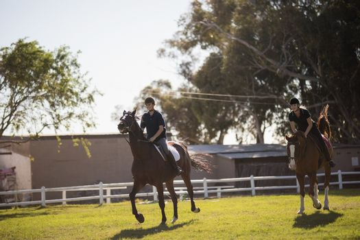 Friends riding horse at equestrian center