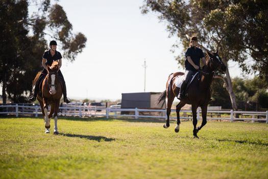 Women riding horse at equestrian center