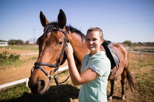 Portrait of female jockey fastening bridle