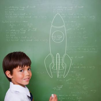 Rocket ship against cute pupil holding chalk