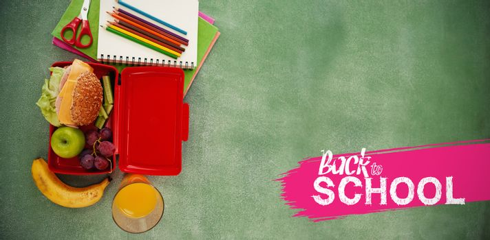 back to school against overhead view of books and pencils with lunch box