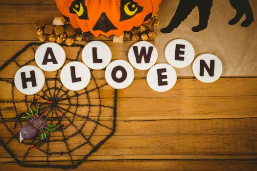 Overhead view of cookies with halloween text and decorations on table