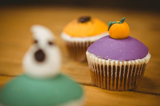 Close up of cup cake with pumpkin on wooden table during Halloween